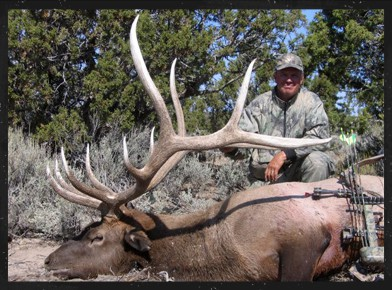 Keven Peterson, President/Founder of Matrix Targets LLC, with dead deer and archery equipment